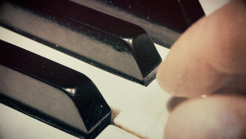 Macro extreme close up of male fingers playing the keys on a piano keyboard. Vintage textures applied.