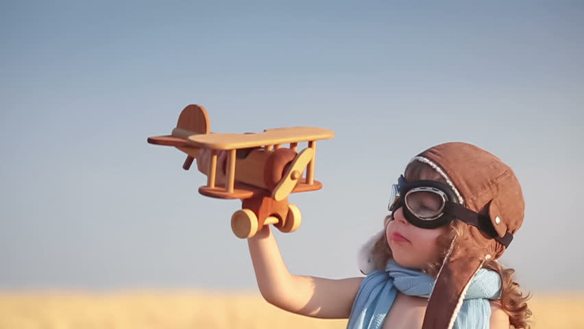 Happy kid playing with toy vintage airplane against summer blue sky background. Travel concept. Slow motion - HD stock video clip