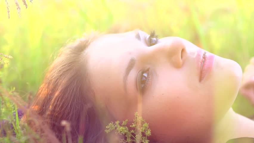 Beautiful Girl Lying on the Meadow and Dreaming. Enjoy Nature. Beauty Woman outdoors. Spring Field. Close up Slow Motion Footage 1920x1080p. Slowmo. High Speed camera shot