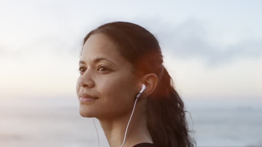 beautiful woman portrait looking at ocean view listening music