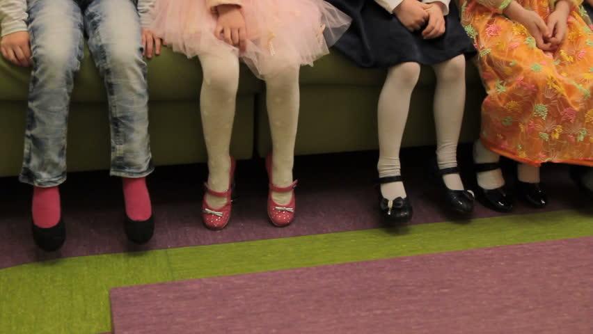 feet of children sitting on the bench