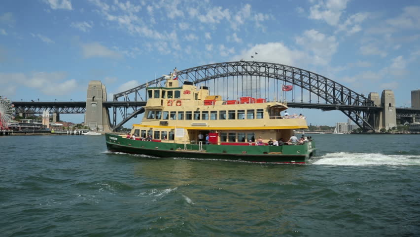 SYDNEY, AUSTRALIA - FEBRUARY 01, 2014: Pan of ferry boat going to Milsons Point, Sydney Harbour bridge and Luna Park.