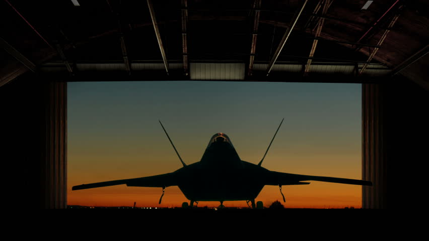 An F-22 Raptor Stealth Fighter is revealed as hangar doors open slowly. - & 1960s: Jet Plane In Flight Ejects Rocket. Supersonic Aircraft In ...