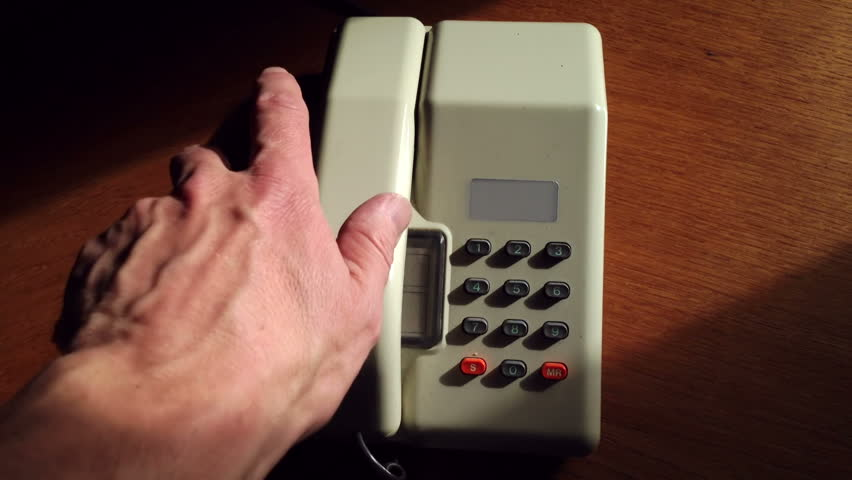 1980s and 1990s style telephone with push buttons picked up, dialled and receiver replaced.