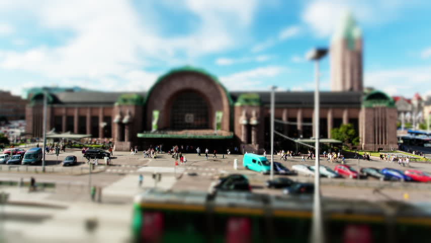 Wide time-lapse tilt-shift shot of tourists and travelers around the Helsinki train Station