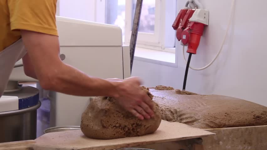 Close footage of man making bread from dough