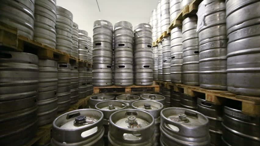 Movement along high rows of metal beer kegs in warehouse