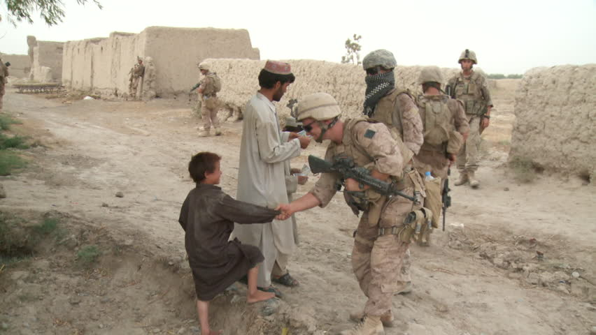 Afghanistan, Circa 2008: Marine on patrol stops and shakes hands with young Afghani boy in rural village in Afghanistan, Circa 2008
