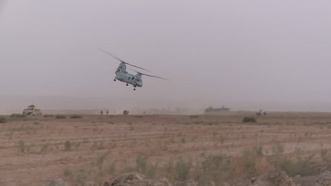 Chinook Helicopter Flies By Left ot Right in the Background of a Humvee Stopped Along a Rural Road in Afghanistan