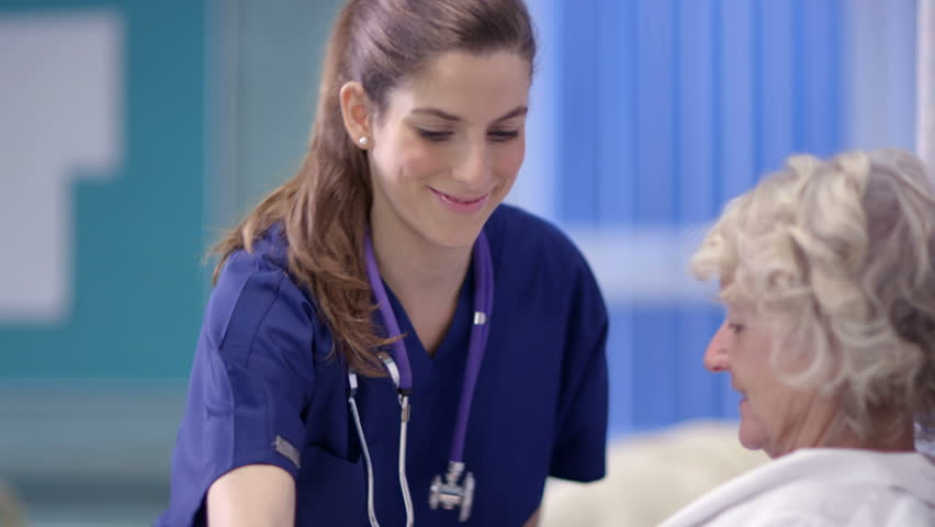 Caring nurse chats with a female patient on a hospital ward.
