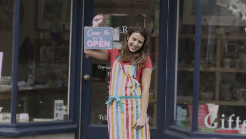 Happy female shopkeeper holds up a sign to show she is open for business   Shutterstock HD Video #5785283