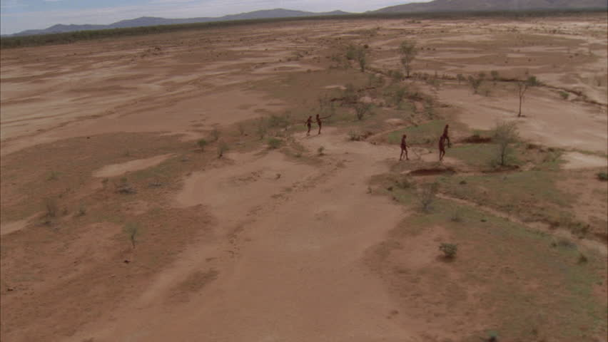 aborigines walk across red sand
