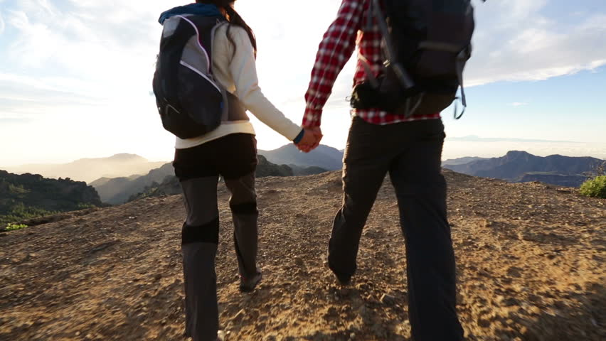 Couple holding hands hiking outdoors at romantic sunset. Hikers man and woman lovers trekking walking with backpacks in trail at sunset in mountains by Roque Nublo, Gran Canaria, Canary Islands, Spain #5838320