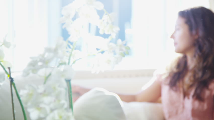 Attractive young woman alone with her thoughts sitting by the window at home.