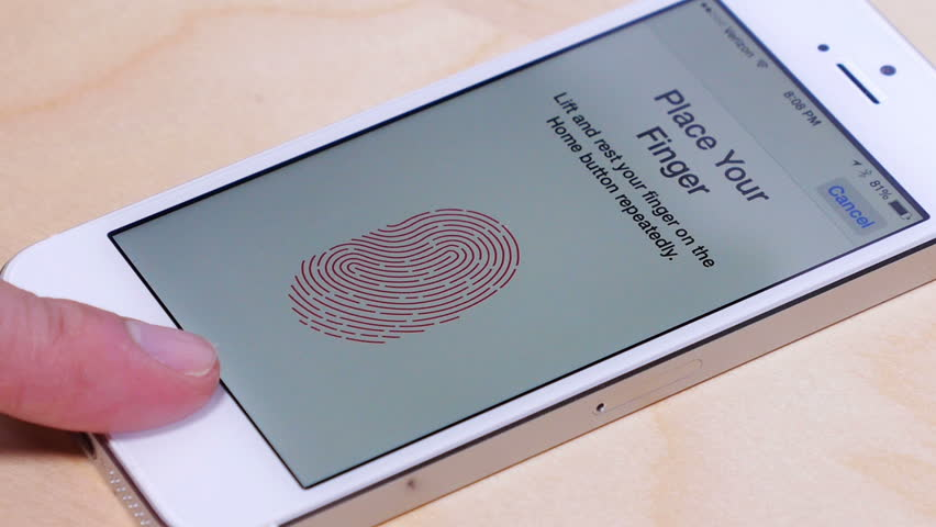 Circa March, 2014: An unidentified person sets up the fingerprint scanner on an Apple iPhone 5S.