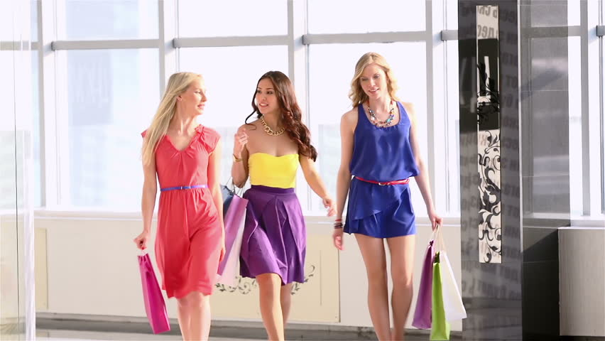 Group of friendly females chatting while walking in the mall