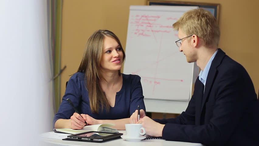4818e97eae00 Young attractive female office worker with man on work meeting. Two people  talking at job interview. Boss and employee discuss issues