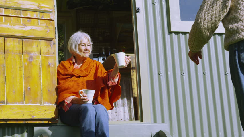 Cheerful senior couple relaxing outside quaint traditional caravan on a bright autumn day.
