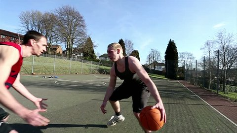 Friends playing basketball outdoors with one player easily defeating the defense and slam dunking