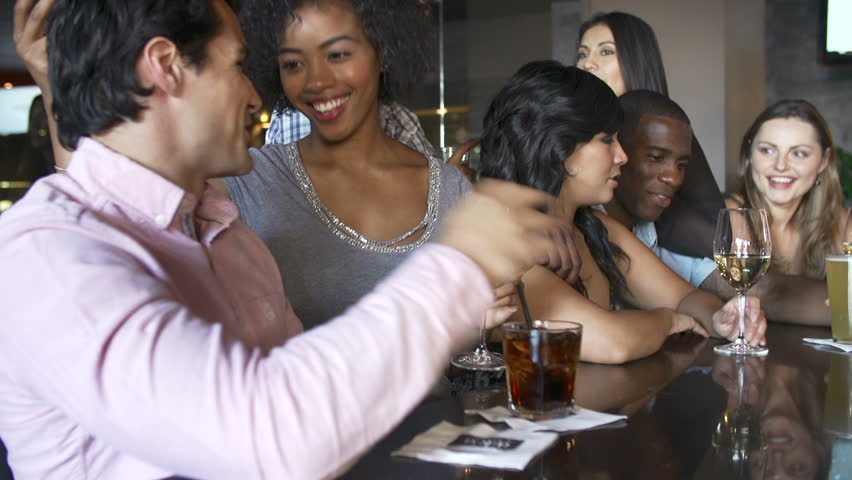 Camera tracks along bar as group of young friends enjoy a night out.Shot on Sony FS700 in PAL format at a frame rate of 25fps   Shutterstock HD Video #5876453