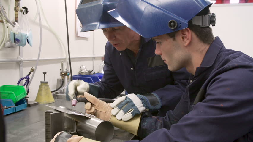 Engineer explaining to apprentice how to use TIG welding machine before they both lower protective face masks.Shot on Sony FS700 in PAL format at a frame rate of 25fps