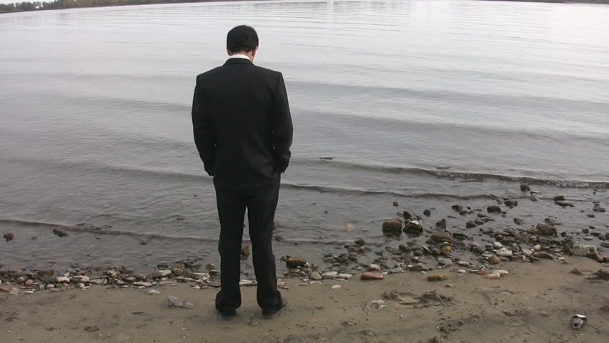 Businessman by the lake. Good shot to represent unemployment.