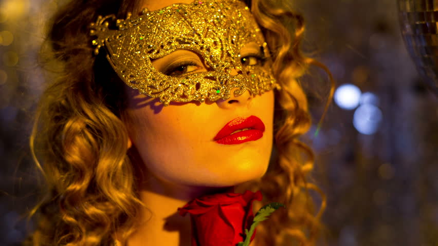 beautiful sexy female in fantastic gold catsuit in lounge bar setting with mask and a rose. Useful for parties, clubs and events