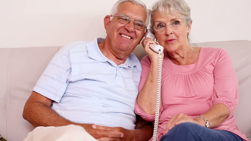 Senior couple sitting on sofa talking on the phone at home in the living room