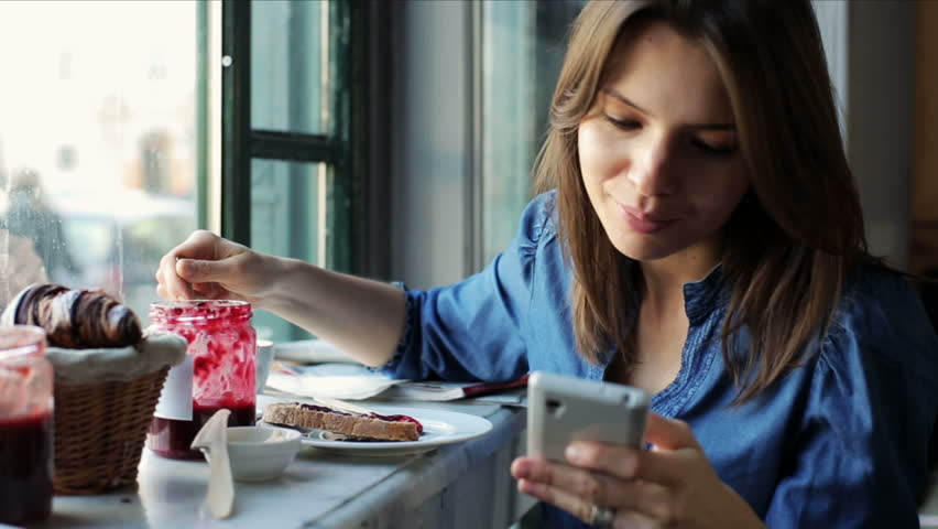 Woman texting, sending sms on smartphone in bar