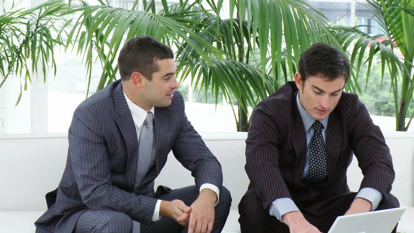 Footage in high definition of two businessmen sitting on sofa working with a laptop   Shutterstock HD Video #591913