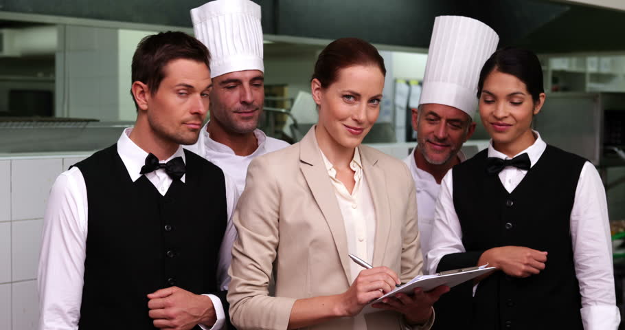 Restaurant Kitchen Manager serious restaurant staff with manager looking at camera in a