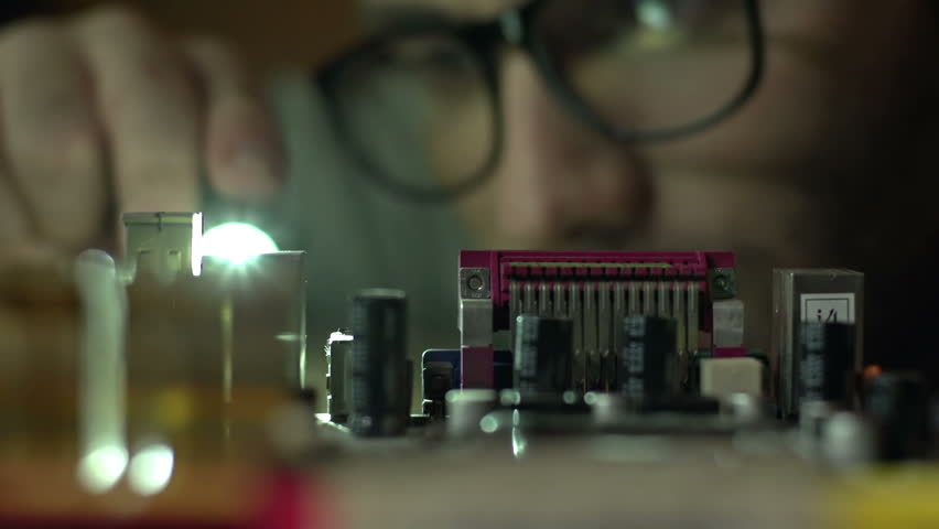 Close-up on the main-board of computer inspected by a man with a flash-light
