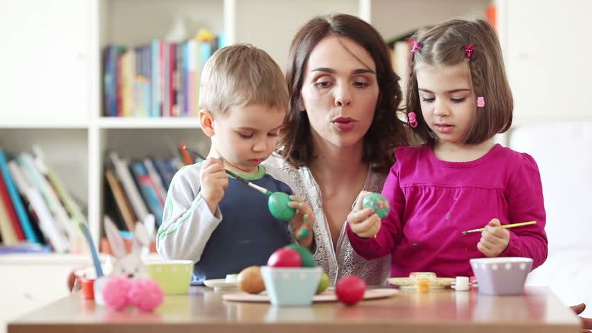 Kids painting Easter eggs with their mother