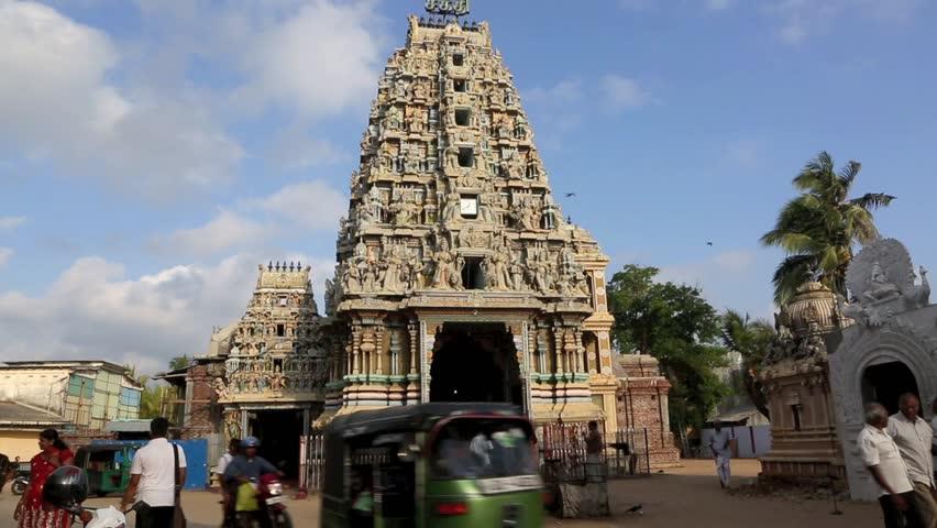 TRINCOMALEE, SRI LANKA - MAR 26: Early morning traffic and Hindu people preying at Sri Pathrakali temple on March 26, 2014 in Trincomalee, Sri Lanka