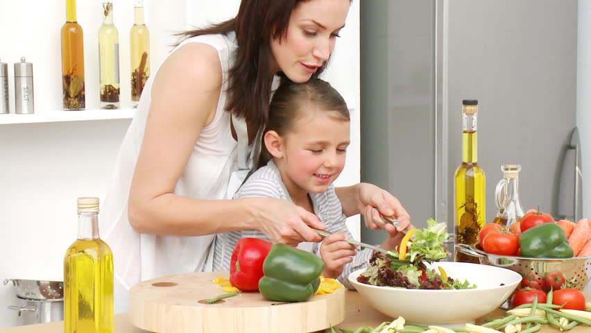 Beautiful mother and daughter preparing a salad in the kitchen. Concept of nutrition. Footage in high definition