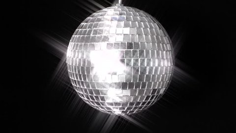 Mirror Ball 1. A mirror ball, also known as a disco ball, spinning against black. A star filter added for a pleasing shine and reflective effect.