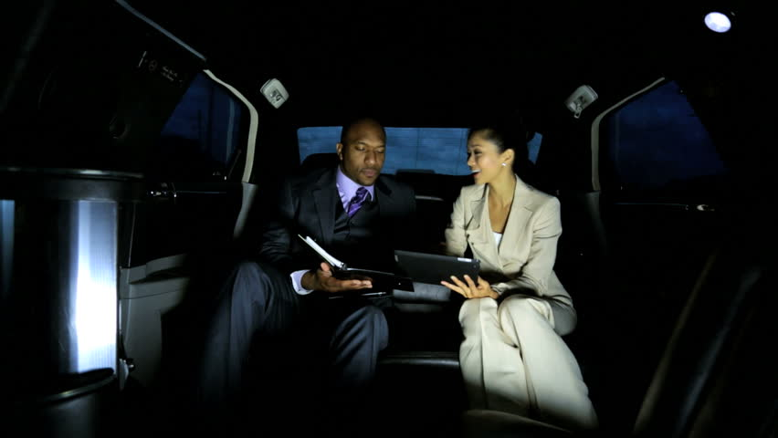 Male female multi ethnic company executives travelling important business meeting by luxury limousine meet and greet service - Male Female Business People Being Driven Luxury Limousine