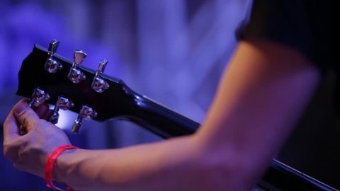 Medium shot of musician's arm tuning electric guitar backstage at concert