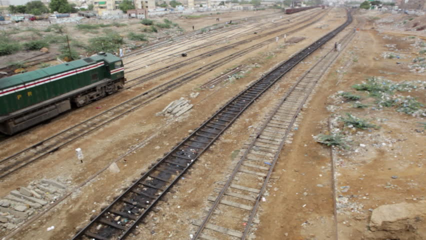 KARACHI, PAKISTAN: A passenger train moving across a wide bed of tracks. | Shutterstock HD Video #6016853
