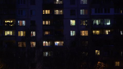 Light in the windows of a multistory building. Minsk. Time lapse. Defocus out