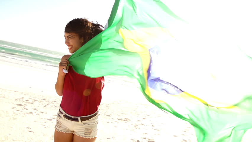Brazilian woman cheering for brasil with flag in slow motion