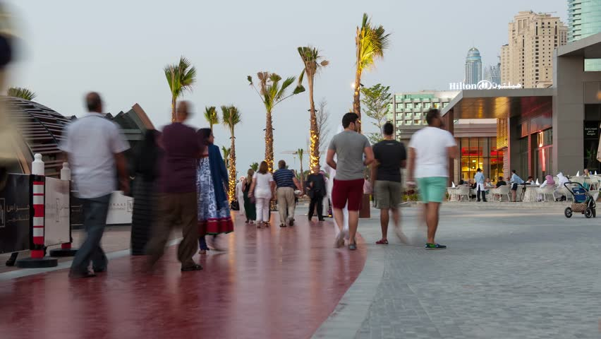 DUBAI, UAE - MARCH 27, 2014: People walking on The Walk (Jumeirah Beach Residence). The Walk is a 1.7 kilometer strip at ground level of the Jumeirah Beach Residence complex opened officially in 2008.