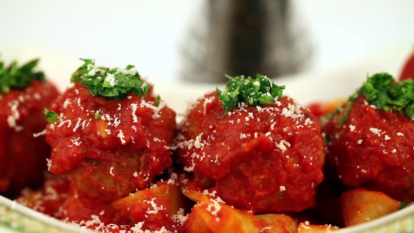 Meatballs Parmesan - Stock footage of grating parmesan above hot meatballs and pasta.