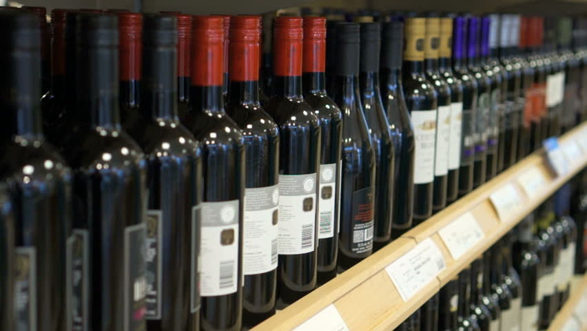 A hand takes a bottle of wine from the shelf. Shopping, and choosing a bottle of wine from the large selection to buy, grabbing it from the display rack.