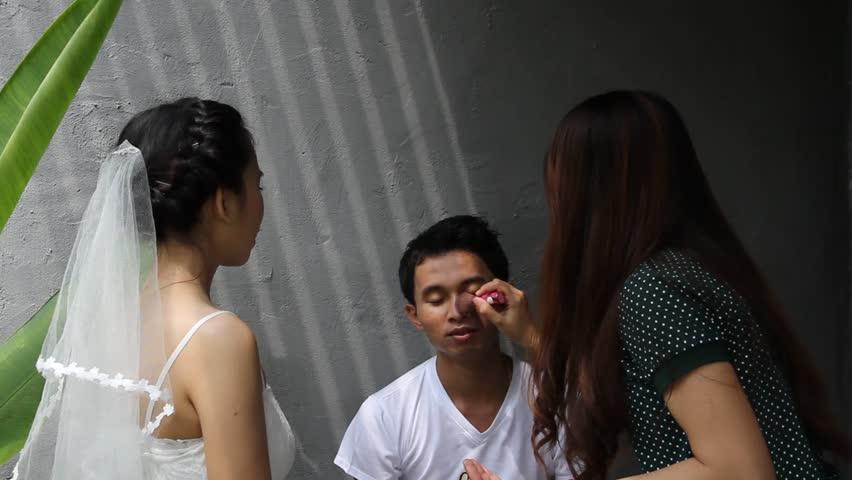 Makeup artist apply makeup to an attractive young groom | Shutterstock HD Video #6053249