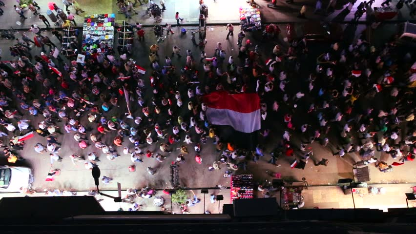 View from overhead looking straight down on protestors marching in the streets of Cairo, Egypt at night.