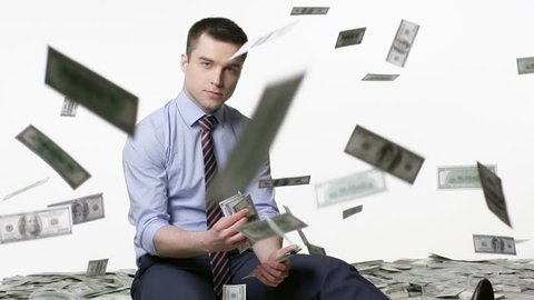 Man sitting and counting money, bills falling from above