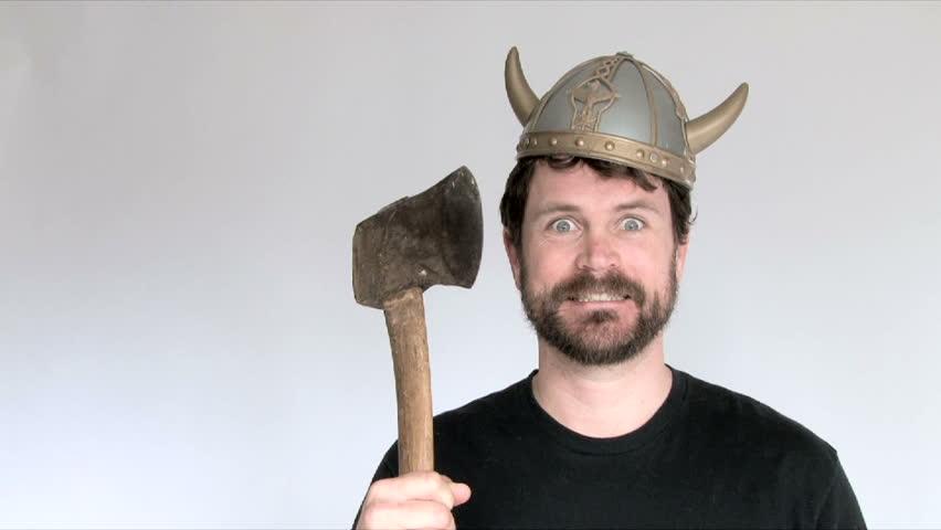 Model released man in studio wearing viking helmet wielding axe.