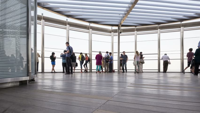 DUBAI, UAE - MARCH 29, 2014: People walking on Burj Khalifa observation terrace. Burj Khalifa is the tallest man-made structure in the world, at 829.8 m (2,722 ft). Time lapse movie. | Shutterstock HD Video #6085556