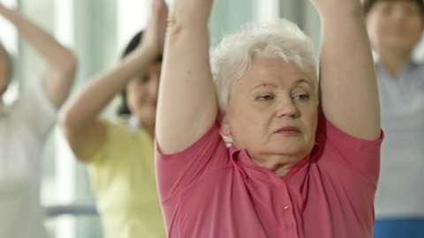 Focus shifting from elderly lady in pink t-shirt to woman in green